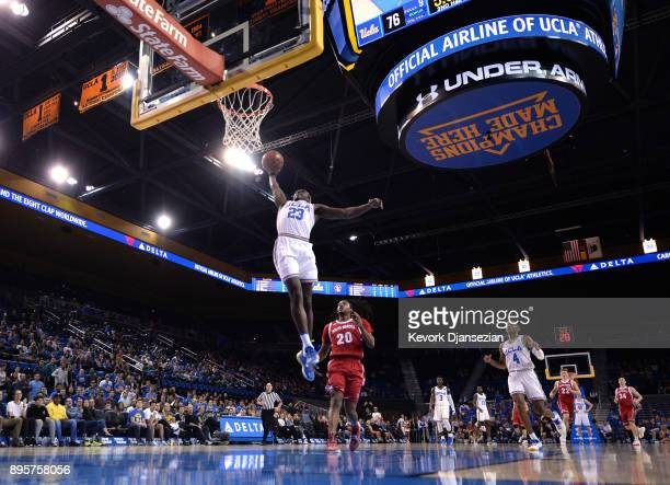 Prince Ali of the UCLA Bruins slam dunks against Brandon Armstrong of the South Dakota Coyotes during the second half at Pauley Pavilion on December...