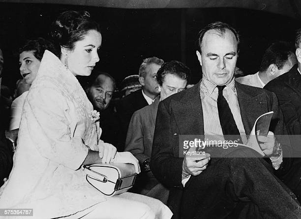 Prince Aly Khan reading the item catalogue sitting next to actress Elizabeth Taylor at an auction of his paintings in Paris May 23rd 1957
