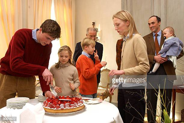 Prince Amedeo blows out the candles on his birthday cake in presence of Queen Paola King Albert Prince Joachim Princess LaetitiaMaria Prince Lorenz...