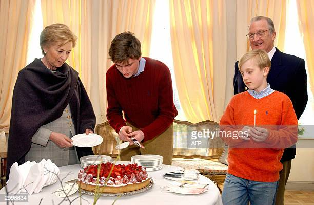 Prince Amedeo cuts a part of his cake for his grandmother Queen Paola in front of his grandfather King Albert II and his brother Joachim to celebrate...