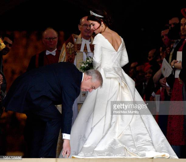 Prince Andrew, Duke of York adjusts daughter Princess Eugenie's wedding dress train as they arrive at St George's Chapel ahead of her and Jack...