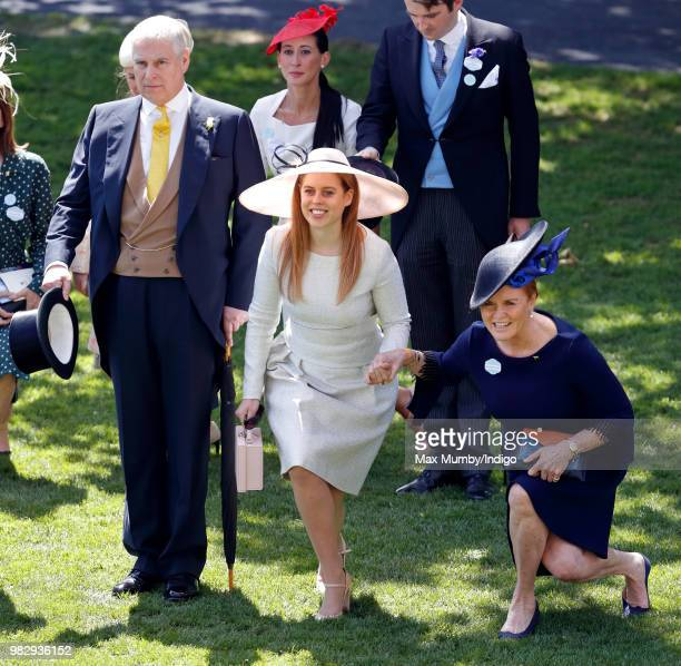 Prince Andrew Duke of York doffs his top hat whilst Princess Beatrice and Sarah Duchess of York curtsy to Queen Elizabeth II as she and her guests...