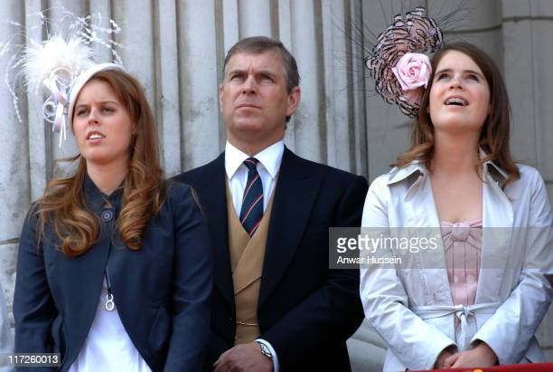 Prince Andrew Duke of York stands between his daughters Princess Beatrice and Princess Eugenie wearing teeth braces on the balcony of Buckingham...