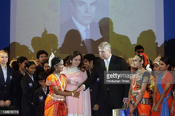 Prince Andrew Duke of York talks to school children as Nita Ambani looks on during his visit to the Dhirubhai Ambani International School on May 2...