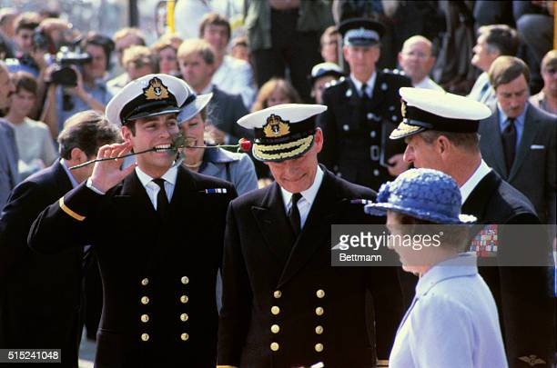 Prince Andrew holds a rose in his mouth, as he and his mother and father, Queen Elizabeth and Prince Philip return from the Falklands on board the...