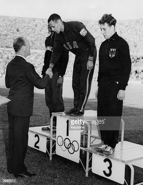 Prince Axel of Denmark presents a gold medal to Malvin Whitfield of the USA winner of the 800 metres final at the 1952 Helsinki Olympics In second...