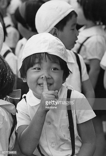 Prince Aya of Japan the second son of Crown Prince Akihito and Princess Michiko gesturing with his finger on his nose at his kindergarten sports day...