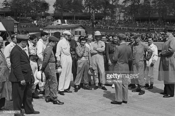 Prince Bira of Siam, driver of the White Mouse Stable Maserati 8CM stands at the centre of the drivers meeting as Earl Howe looks on before the start...