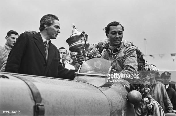 Prince Bira of Siam driver of the White Mouse Stable Maserati 8CM celebrates with the trophy after winning the JCC International Trophy race on 6th...