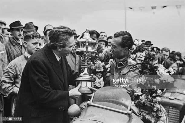 Prince Bira of Siam, driver of the White Mouse Stable Maserati 8CM celebrates with the trophy after winning the JCC International Trophy race on 6th...