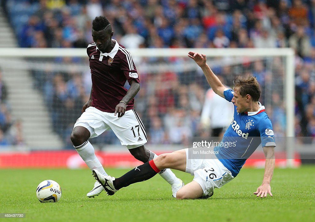 Prince Buaben (L) of Hearts vies with Marius Zaliukas of Rangers during the Scottish Championship Opening League Match between Rangers and Hearts, at Ibrox Stadium on August 10, 2014 Glasgow, Scotland.