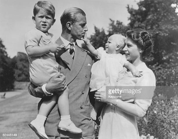 Prince Charles aged two, in the arms of his father, the Duke of Edinburgh. His mother, the then Princess Elizabeth, holds Princess Anne, as they walk...