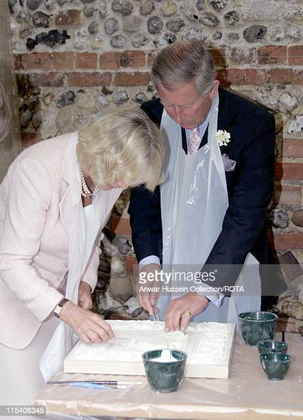 Prince Charles and Camilla Duchess of Cornwall have a go at Pargeting on a visit to the Suffolk village of Lavenham on July 22 2005