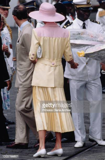 Prince Charles and Diana, Princess of Wales disembark from the Royal Yacht Britannia in Douala, Cameroon, March 1990. Diana is wearing a pink and...