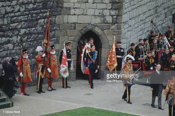 Prince Charles and his cortège emerge from the Chamberlain Tower, before his investiture as Prince of Wales at Caernarfon Castle, Gwynedd, Wales, 1st...