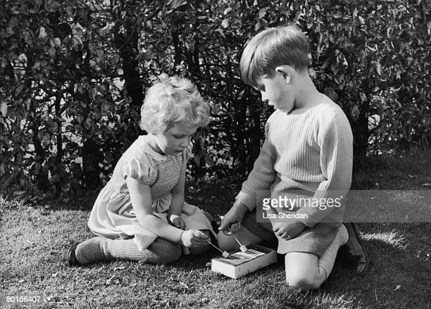 Prince Charles and Princess Anne play with a xylophone in the garden of the Royal Lodge, Windsor, April 1954.