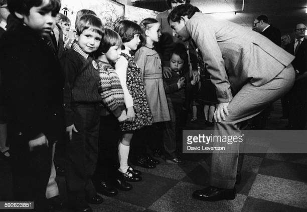 Prince Charles bending down to talk to a group of children during a visit to Deeside Leisure Centre October 27th 1981