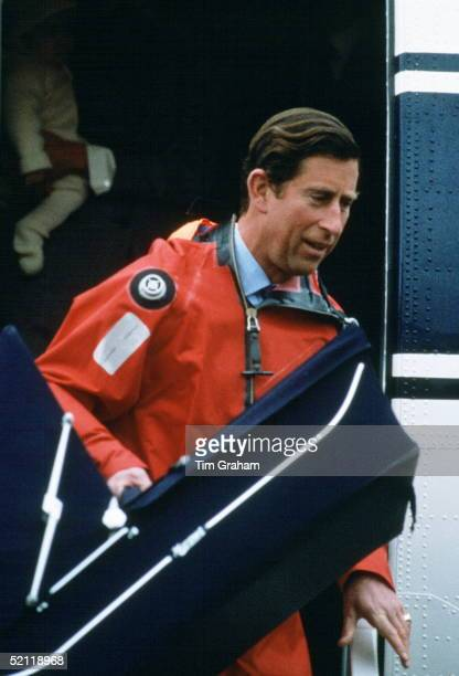 Prince Charles Carrying A Carrycot For His Son From The Royal Flight Aeroplane He Is Wearing Wet Weather Gear For A Visit To A North Sea Oil Rig