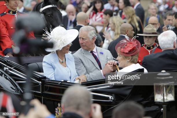 Prince Charles center right and Camilla Duchess of Cornwall center left arrive in a horse drawn carriage during the Canada Day event on Parliament...