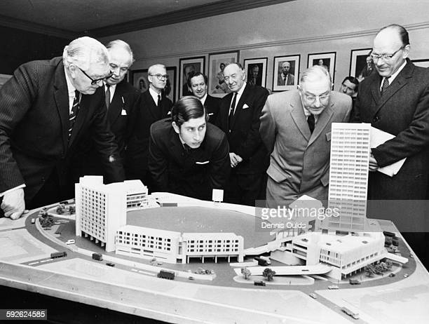 Prince Charles closely inspecting a model of the proposed development of the famous Oval Cricket Ground, with President M J C Allom, Secretary...