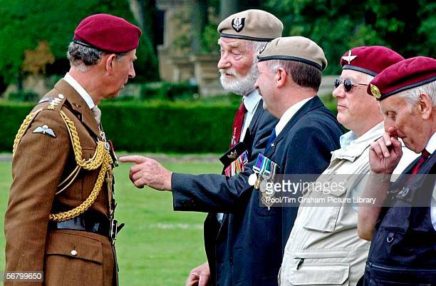 Prince Charles colonelinchief of the Parachute Regiment talks to veterans after presenting new Colours to the Volunteer Battalion at Hardwick Hall