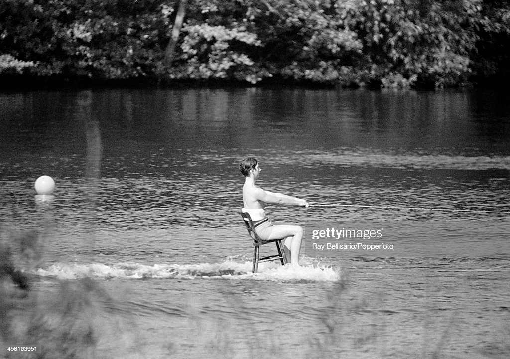 Prince Charles demonstrating his water-skiing skills with a challenge set by his uncle Lord Snowdon (Tony Armstrong-Jones) at Sunninghill Park in Windsor, 18th June 1970. Lord Snowdon, himself a very skilled water-skiier, challenged the Prince to ski whilst sitting on a dining chair which was placed on a table top (partly hidden). This image is one of a sequence taken by Ray Bellisario who was credited with being the 'original paparazzo' and someone who frequently upset the Royal Family with his informal and often unwelcome style of photography.