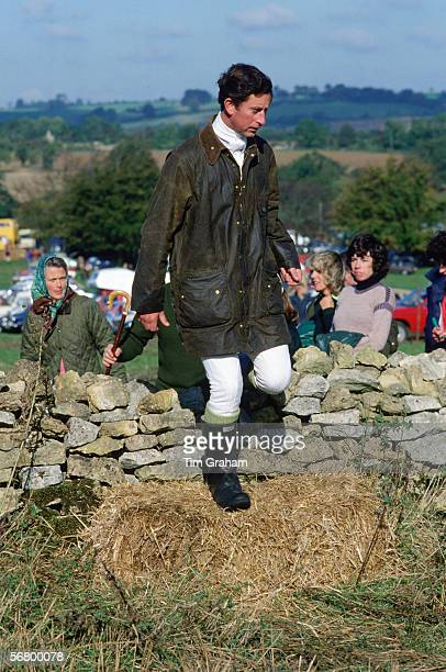 Prince Charles dressed in a Barbour jacket and wellington boots steps over a stone wall whilst watched by Lady Sarah Keswick and Camilla ParkerBowles