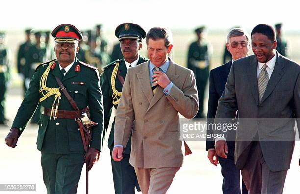 Prince Charles, flanked King Letsie III and Lesotho Defense Forces Commander Makhula Mosakenj , walks past the guards of honor at Moshoeshoe airport...