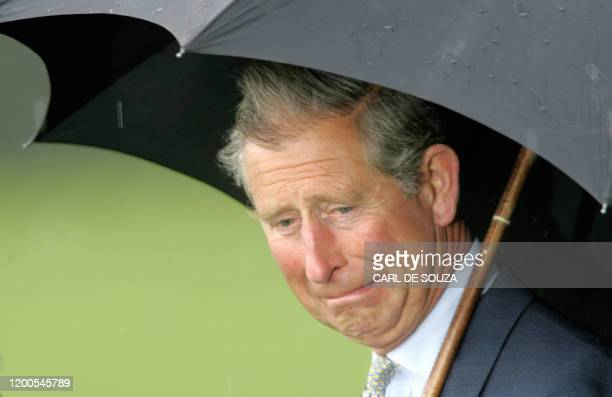 Prince Charles grimaces as he walks during the opening of a sports pavillion at Hyde Park in London, 27 April 2005.