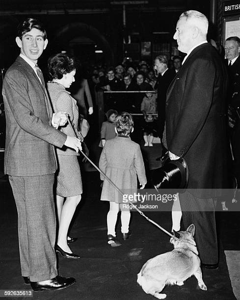 Prince Charles holding a pet corgi on a leash with Princess Margaret and her son Viscount Linley in the background arriving at Liverpool Street...