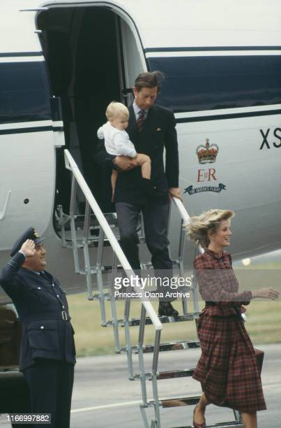 Prince Charles holding Prince William as he disembarks from The Queen's Flight behind Diana Princess of Wales at Aberdeen airport in Scotland August...
