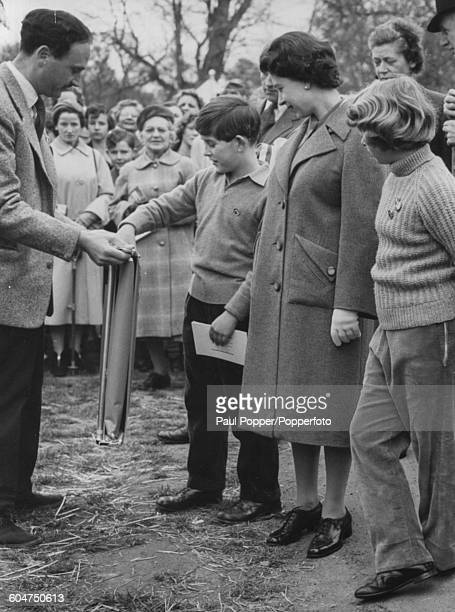 Prince Charles inspects a folding picnic chair watched by Queen Elizabeth II and Princess Anne at a temporary shop during the Badminton Horse Trials...