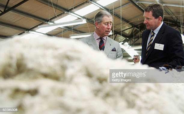 Prince Charles inspects a table of merino fleece with John Brakenridge CEO of The New Zealand Merino Company during a visit to Moutere Sheep Station...