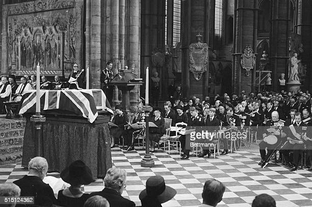 Prince Charles is shown reading the lesson from the lectern with members of the Royal Family seated below him The Queen Duke of Edinburgh Queen...
