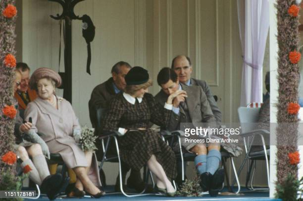 Prince Charles kisses the hand of Diana, Princess of Wales at the Braemar Highland Games in Scotland, September 1982. The Queen Mother is on the...