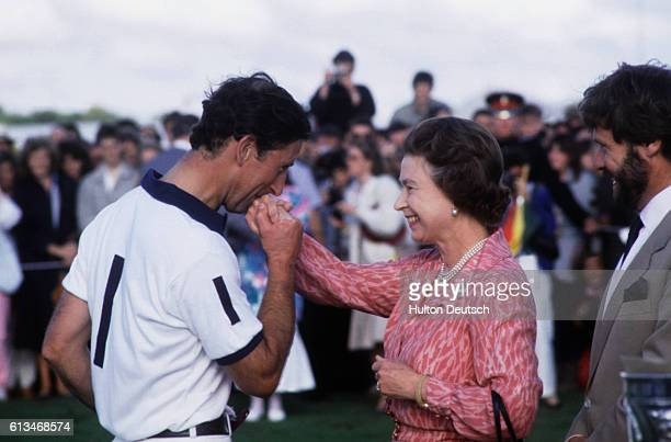 Prince Charles kisses the hand of his mother the Queen after the Cartier Polo Match