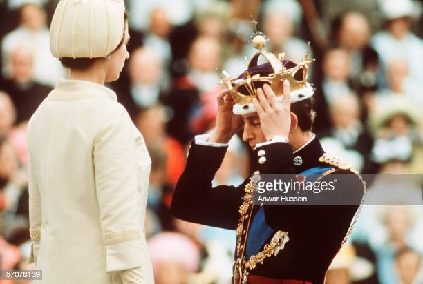 Prince Charles kneels before Queen Elizabeth as she crowns him Prince of Wales at the Investiture at Caernarvon Castle on July 1, 1969 in Wales.