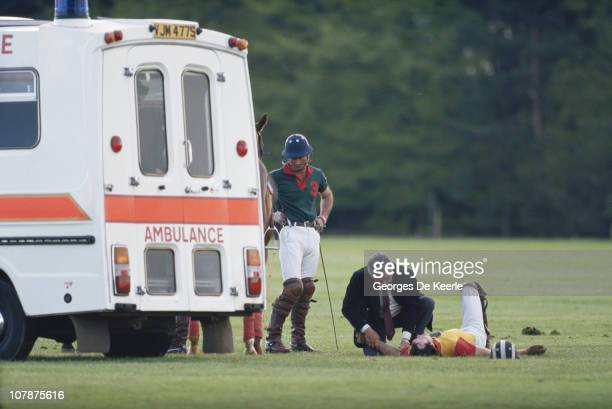 Prince Charles looks on as a doctor examines an injured player at a polo match UK 2nd May 1988