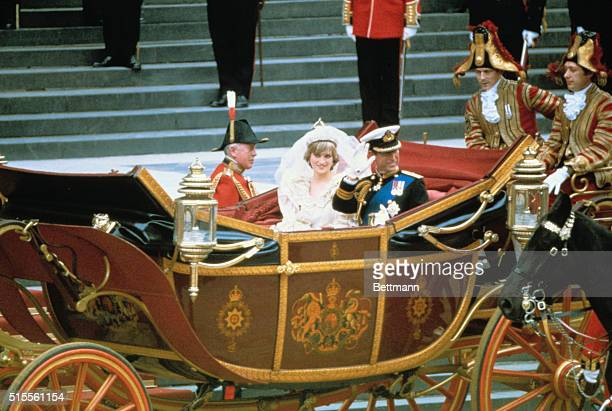 Prince Charles of Wales and his new bride, the former Lady Diana Spencer, riding in an open carriage after the wedding ceremony.