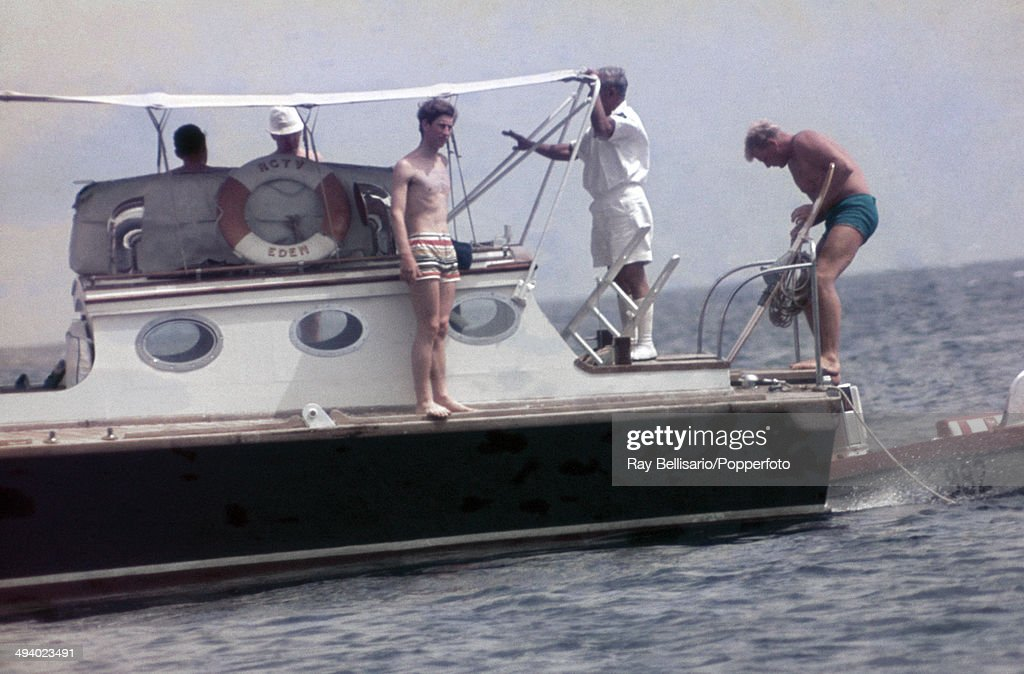 Prince Charles (wearing bathing trunks, left) on board a yacht during a holiday in Malta on 9th July 1969. This image is one of a series taken by Ray Bellisario who was credited with being the 'original paparazzo' and someone who frequently upset the Royal Family with his informal and often unwelcome style of photography.