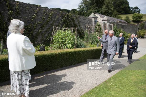 Prince Charles Prince of Wales accompanied by Anthony Tavernor owner and restorer of the Plas Cadnant Hidden Gardens visits the gardens during The...