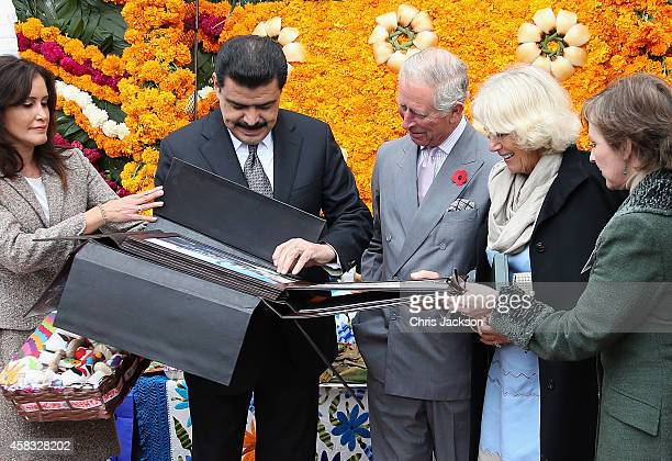 Prince Charles Prince of Wales and Camilla Duchess of Cornwall are shown a photo album as they visit the Pasty Museum in Real del Monte on the Day of...