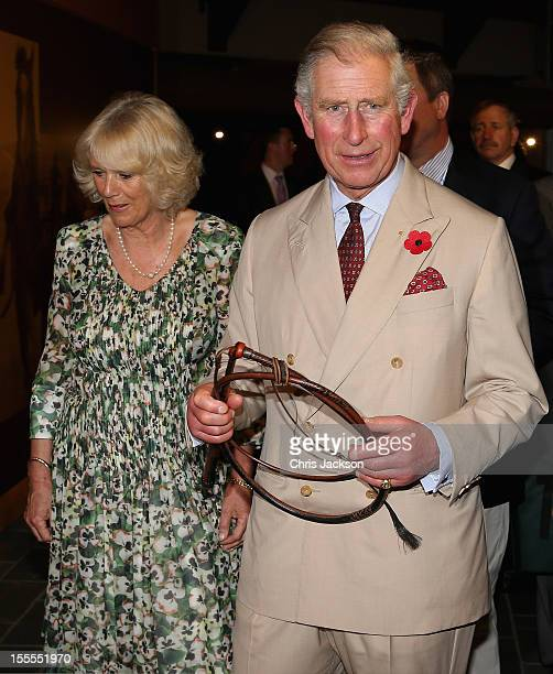 Prince Charles Prince of Wales and Camilla Duchess of Cornwall are presented with a cattle whip as they visit the Cattle Rancher's Hall of Fame on...