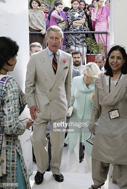 Prince Charles Prince of Wales and Camilla Duchess of Cornwall are greeted by teachers as they enter a public administration lesson at Fatima Jinnah...