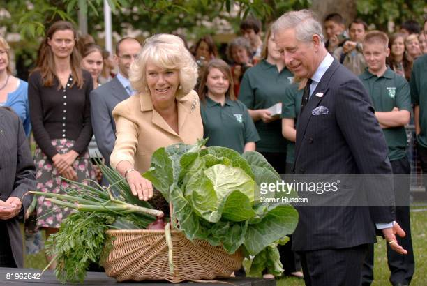 Prince Charles, Prince of Wales and Camilla, Duchess of Cornwall are presented with vegetables from the allotment as they visit the 'Dig for Victory'...
