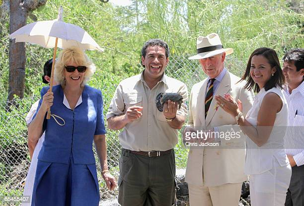 Prince Charles Prince of Wales and Camilla Duchess of Cornwall are presented with a tortoise called William during a tour of the Darwin Research...