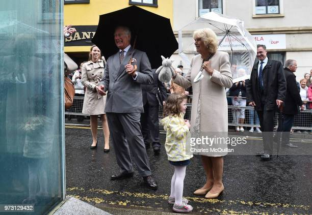 Prince Charles Prince of Wales and Camilla Duchess of Cornwall are presented with a bunny rabbit by Matilda Callaghan on the exact spot of the Omagh...