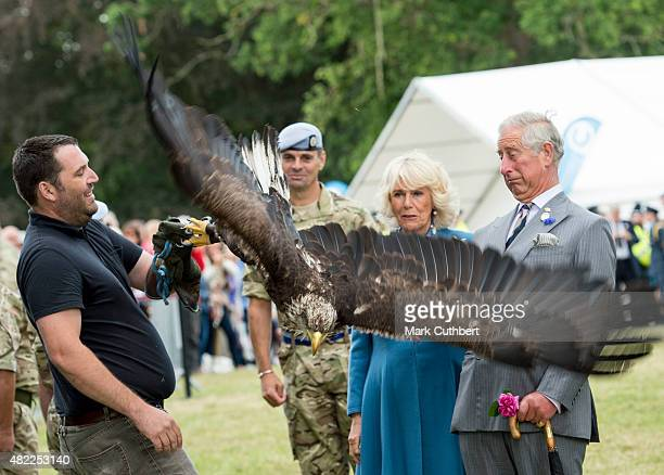 Prince Charles Prince of Wales and Camilla Duchess of Cornwall looking at Zephyr the Bald Eagle with his handler Andy during a visit the Sandringham...