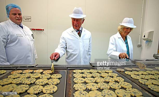 Prince Charles Prince of Wales and Camilla Duchess of Cornwall flip Welsh Cakes on hot plates as they tour of the Village Bakery on July 7 2015 in...
