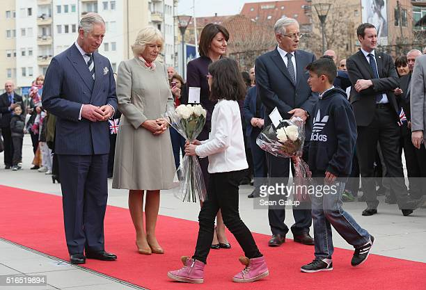 Prince Charles Prince of Wales and Camilla Duchess of Cornwall receive flowers from children that the royal couple laid at a memorial to people still...